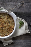 vegetables au gratin on casserole with fork on wooden table