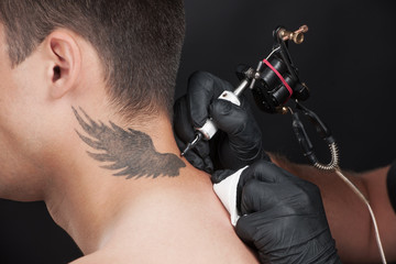 professional tattooist drawing beautiful wings.