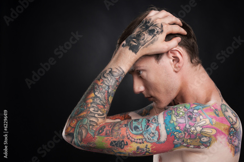 man with tattoo holding head with hands.