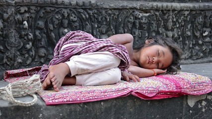young girl sleeping in angkor wat temple, cambodia
