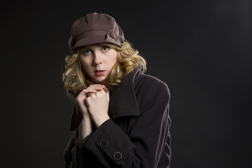 Girl in coat and brown cap on black background. Winter, cold.