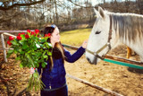 Beautiful young woman with bunch of roses and white horse