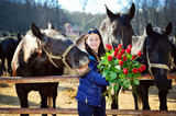 Beautiful young woman with bunch of roses and black horses