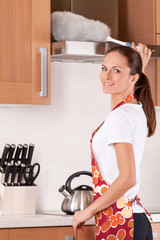 Beautiful young brunette cleaning the kitchen.