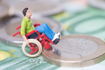 Rollstuhlfahrer auf einem Geldstapel