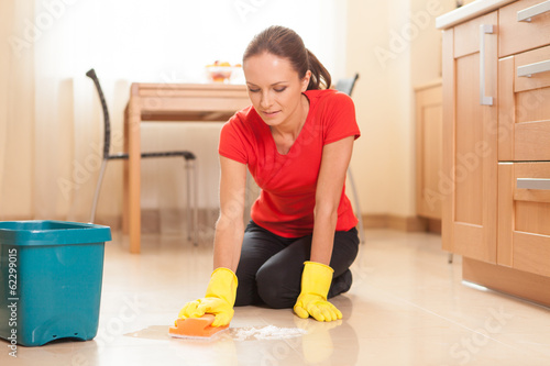 young girl washing floor in kitchen.