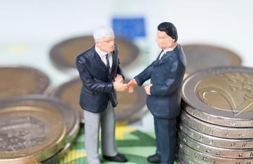 zwei Geschäftsleute mit Münzgeld und Geldscheinen