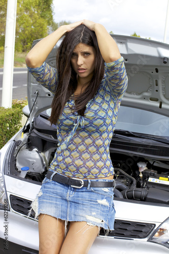 Desperate female model in front of broken car