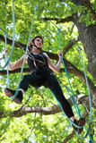 attractive woman climbing in adventure rope park