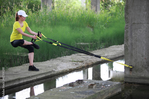woman on the outdoor suspension training at the river