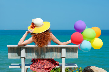 Happy woman in hat with balloons
