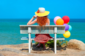 Woman with colored balloons sitting on bench looking at the sea