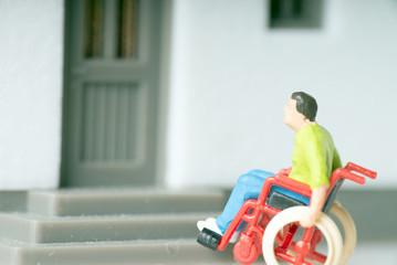 Rollstuhlfahrer vor einem Haus