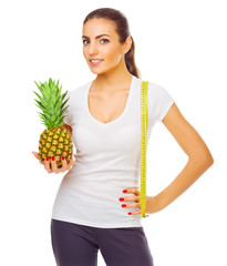 Smiling girl with pineapple and measurement tape isolated