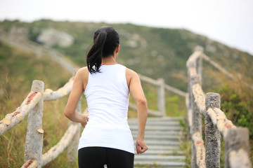 healthy lifestyle woman running up on mountain stairs
