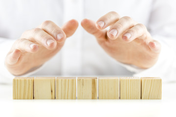 Man holding protective hands above a line of seven blank wooden
