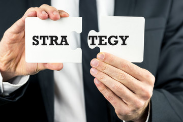 Man holding two pieces of a puzzle with Strategy