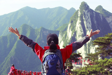 cheering woman hiker on mountain huashan peak