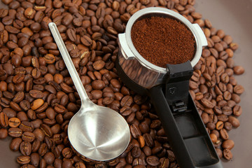 The coffee brewer handle against roasted coffee-bean