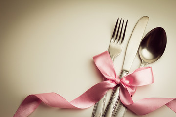 Fork, spoon and knife with decorative ribbon.