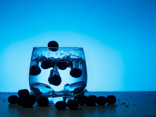 blueberry falling in glass of gin