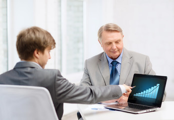 older man and young man with laptop computer