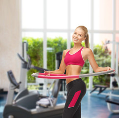 young sporty woman with hula hoop at gym