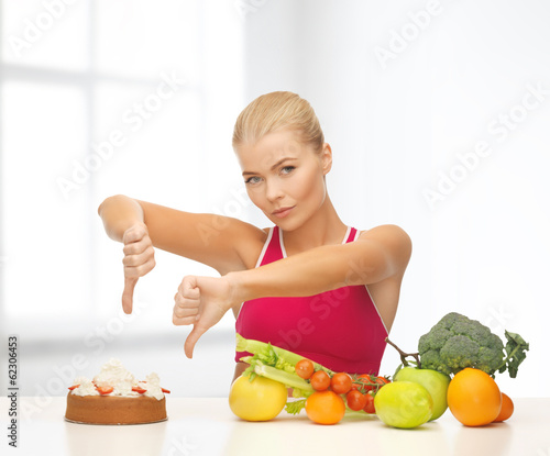 woman with fruits showing thumbs down to cake