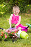 Smiling little girl planting flowers in the garden.