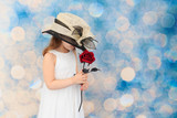 Young child in an oversized, hat holding a red rose