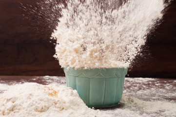 Splash of flour thrown into a bowl