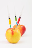 Three color syringes sticking out of two apples
