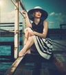 Beautiful woman sitting on old wooden pier