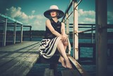 Woman wearing hat and white scarf sitting on old wooden pier