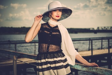 Woman in white hat and scarf standing near old pier rails
