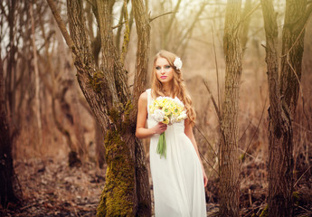 Beautiful bride outdoors in a sunny forest