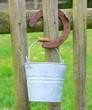 sceau zinc et fer à cheval sur barrière en bois