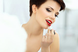 Beautiful Brunette applies lipstick.  LRed lips. Make up