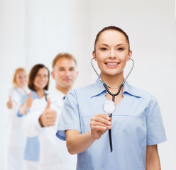 smiling female doctor or nurse with stethoscope