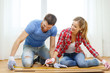 smiling couple measuring wood flooring