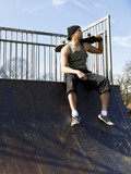 Portrait of a skateboarder sitting at the top of a half pipe