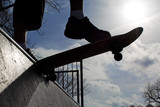 Silhouette feet of a skateboarder about to descend a half pipe
