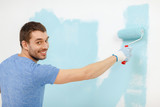smiling man painting wall at home