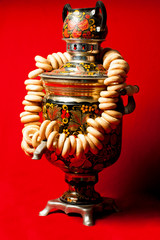 Russian samovar with steering wheels on a red background
