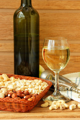 Glass of white wine, nuts, corkscrew and  napkin