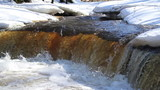A clear water flowing between the snow-covered are a