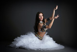 Beautiful belly dancer posing in studio