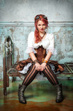 Beautiful steampunk woman on the metal bed