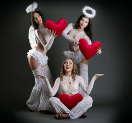 Studio shot of beautiful girls posing as cupids
