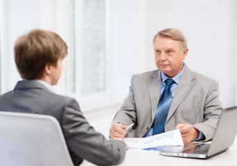 older man and young man having meeting in office